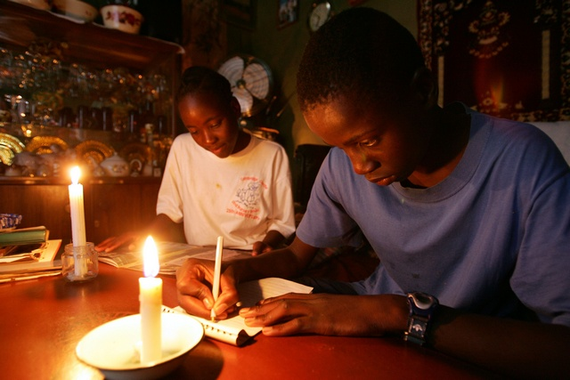 Zimbabwean twins ead and write by candlelight in the capital Harare